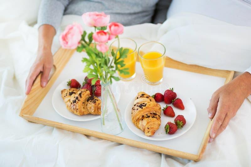 Старшие пары наслаждаясь завтраком в кровати стоковое фото rf