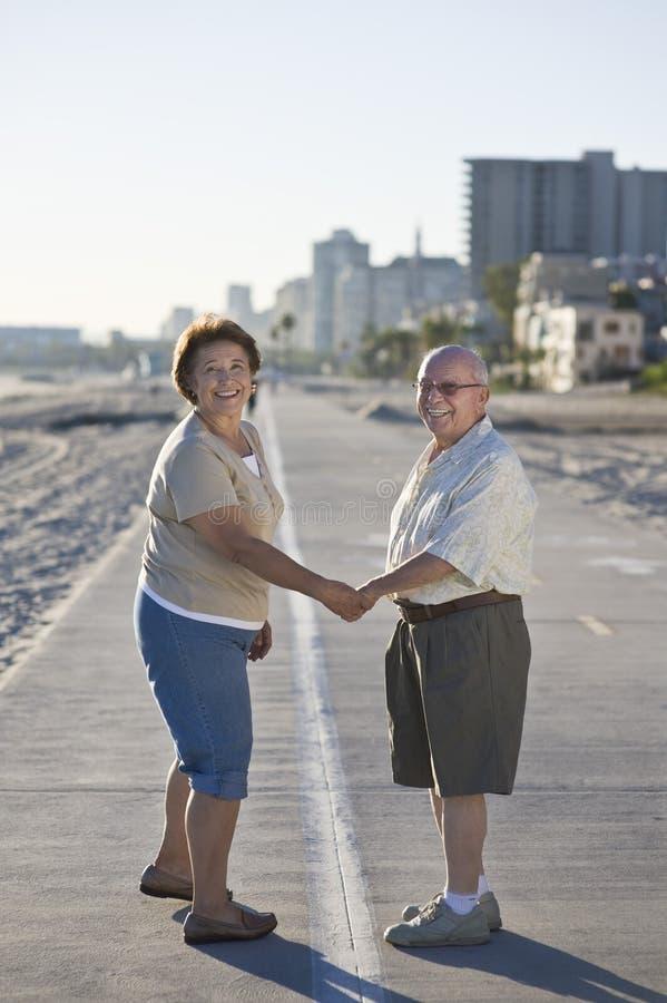 Старшие пары на прогулке держа руки стоковое фото
