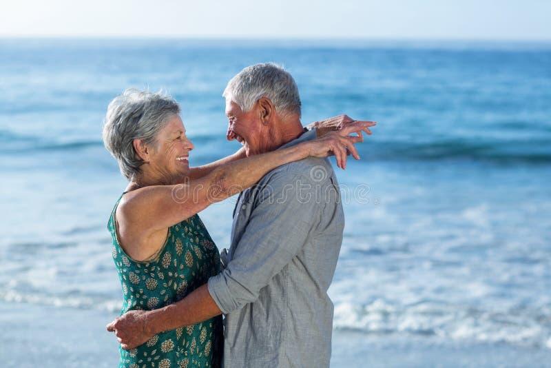 Старшие пары обнимая на пляже стоковые изображения