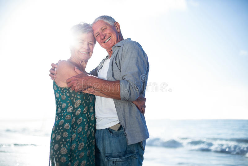 Старшие пары обнимая на пляже стоковая фотография rf