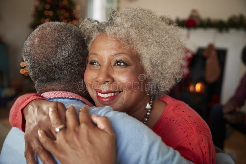 Старшие пары обнимая по мере того как они празднуют рождество дома совместно стоковая фотография rf