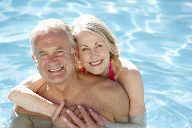 Старшие пары ослабляя в бассейне совместно стоковые фотографии rf