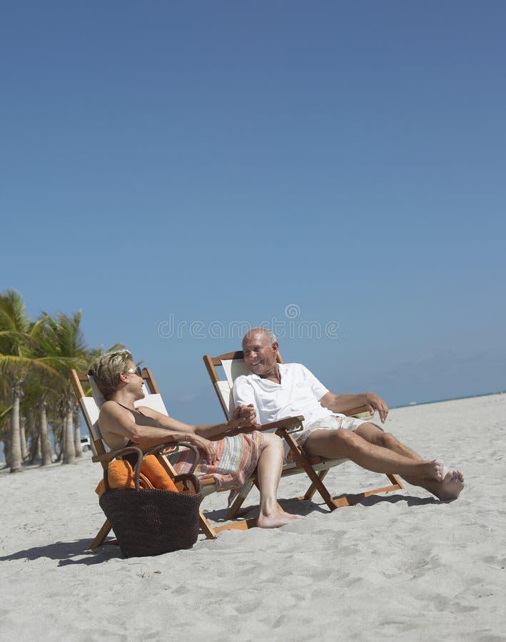 Старшие пары ослабляя на пляже стоковая фотография