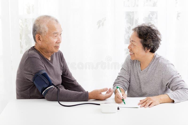 Старшие пары принимая кровяное давление в живущей комнате стоковые фотографии rf