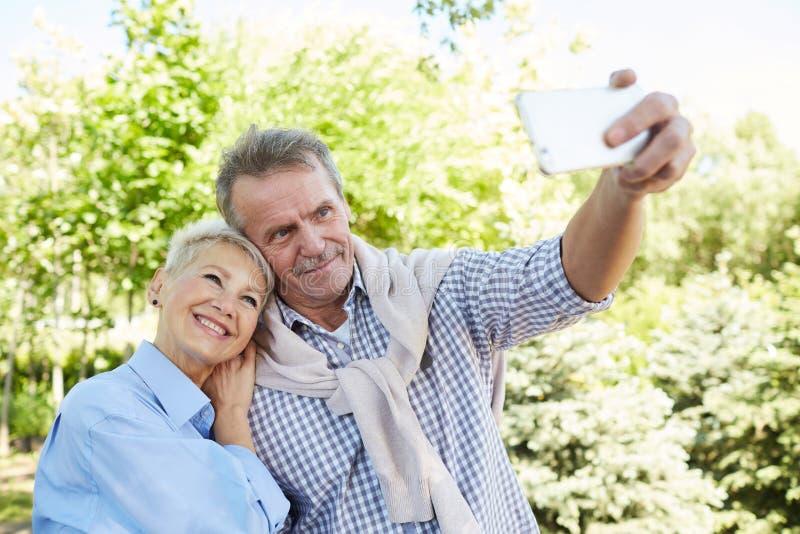 Старшие пары принимая Selfie в парке стоковые изображения