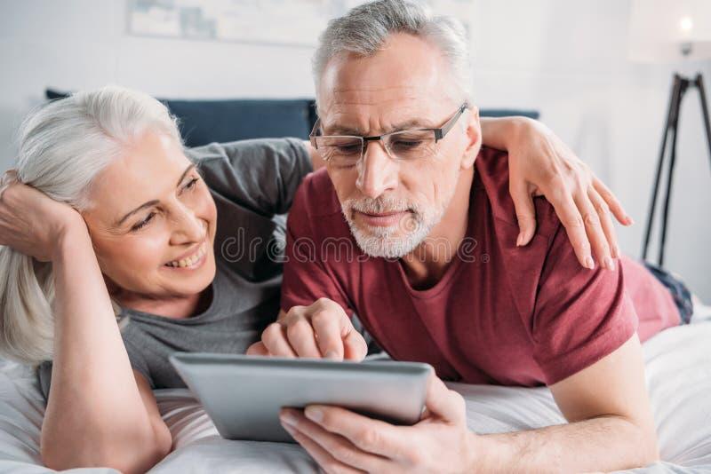 Старшие пары при цифровая таблетка отдыхая в кровати совместно стоковая фотография