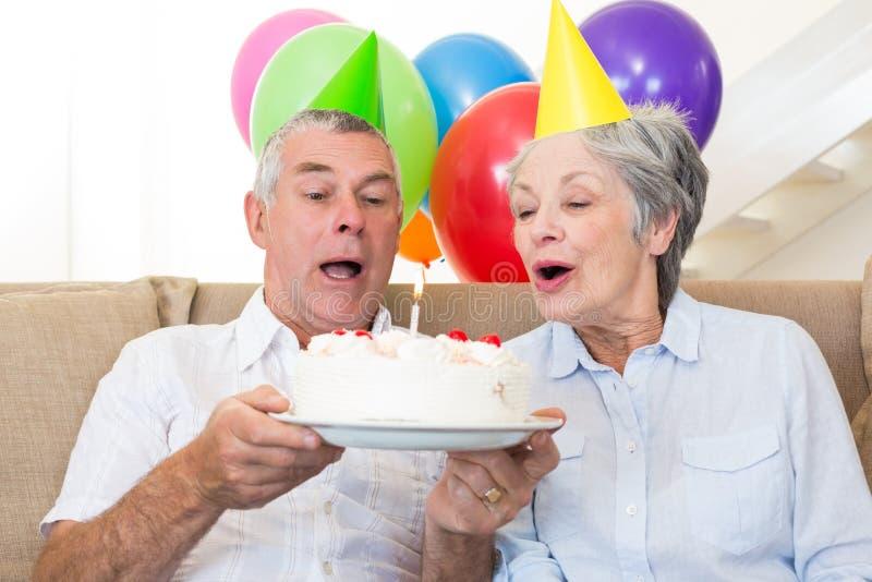 Старшие пары сидя на кресле празднуя день рождения стоковые изображения