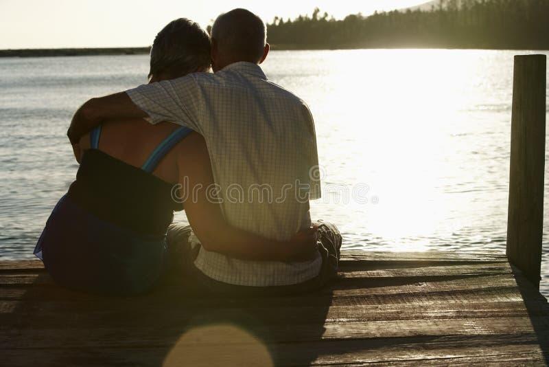 Старшие пары сидя на пристани озером стоковое фото rf