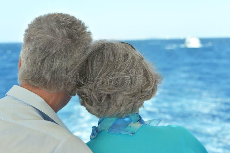 Старшие пары смотря море совместно стоковое фото