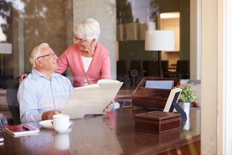 Старшие пары смотря фотоальбом через окно стоковые фото