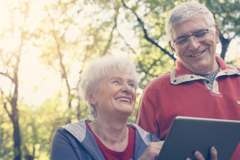 Старшие пары стоя в парке и используя iPod конец вверх стоковые фотографии rf