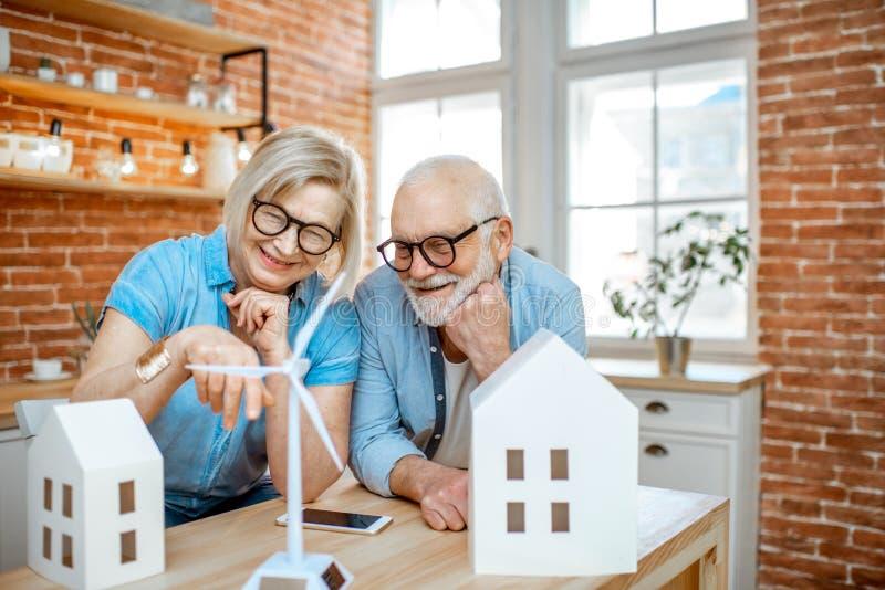 Старшие пары с моделями дома и ветротурбиной игрушки дома стоковое фото rf