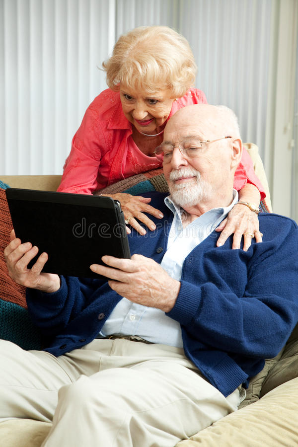Старшие пары с ПК таблетки стоковая фотография