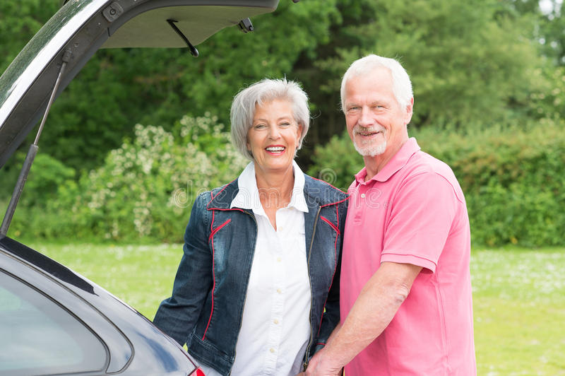 Старшие пары с черным автомобилем стоковые изображения