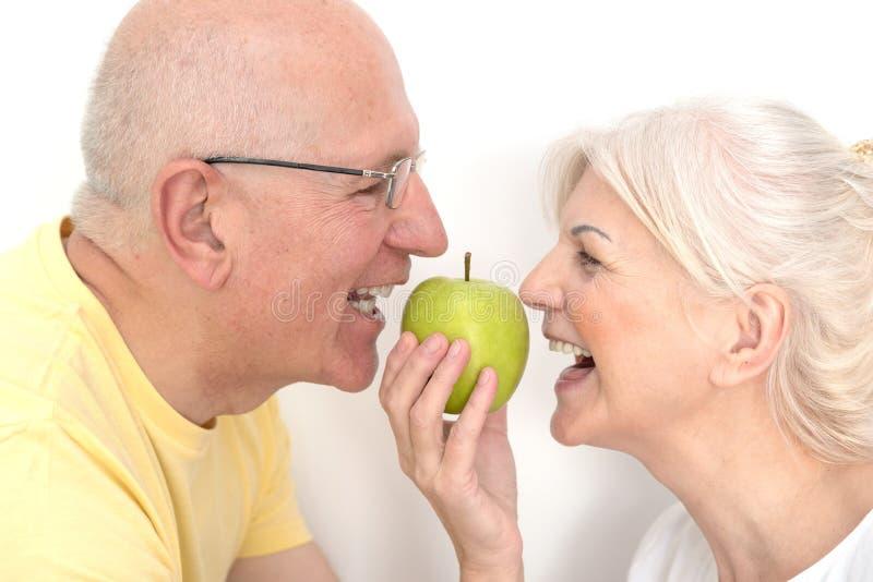 Старшие пары с яблоком, здоровая концепция зубов стоковые фотографии rf