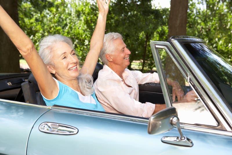 Старшие пары управляя автомобилем спортов стоковые изображения