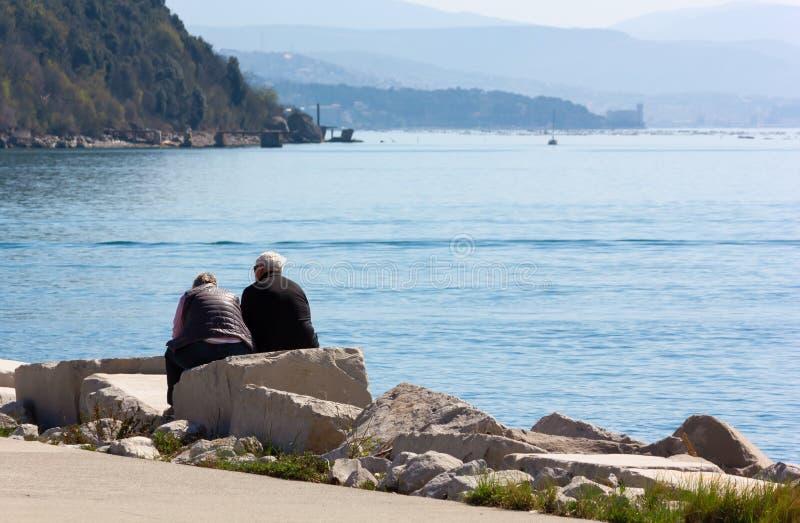 Старшие пары усадили на утес в заливе Sistiana стоковая фотография