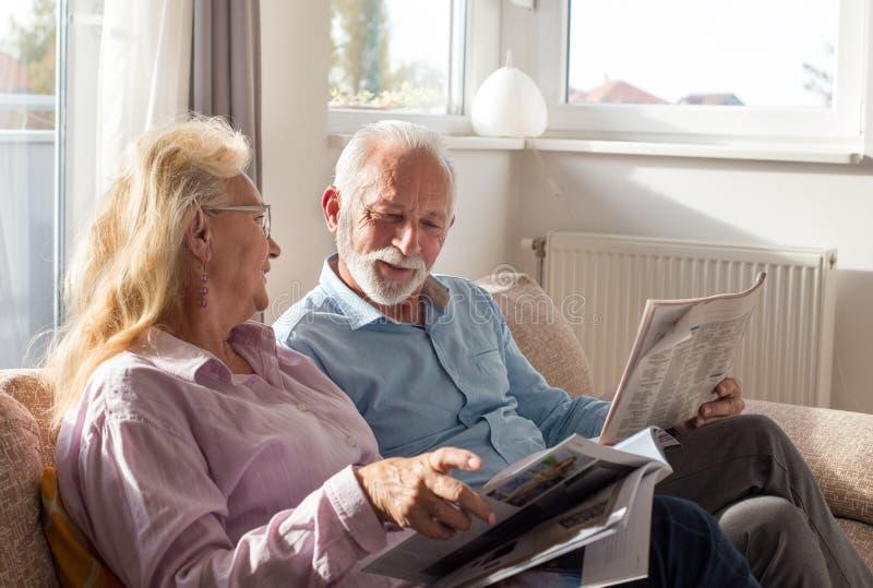 Старшие пары читая дома стоковое изображение rf