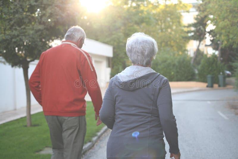 Старшие пары jogging в парке города совместно стоковые изображения