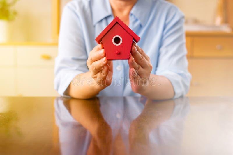 Старшие руки держа домашнюю модель красного цвета для выхода на пенсию, сохраняя концепции денег стоковое изображение