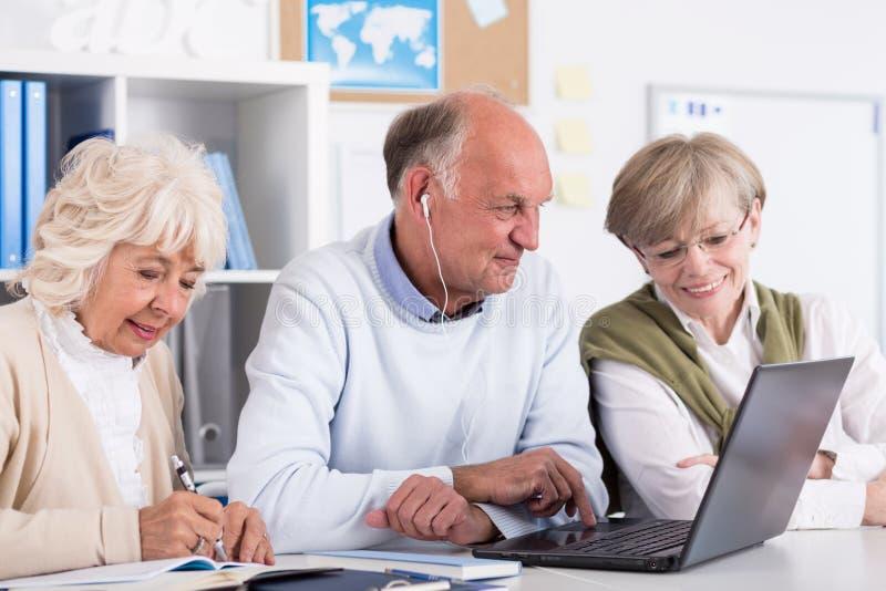 Старшие студенты используя компьютер стоковые фотографии rf