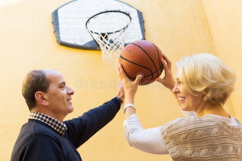Старшие супруги бросая шарик стоковая фотография rf