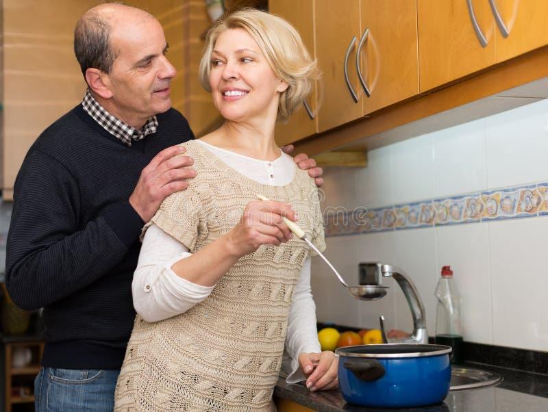 Старшие супруги на современной кухне стоковые фотографии rf