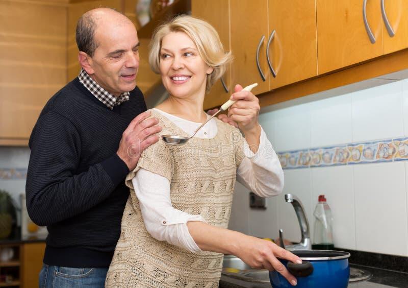 Старшие супруги на современной кухне стоковая фотография