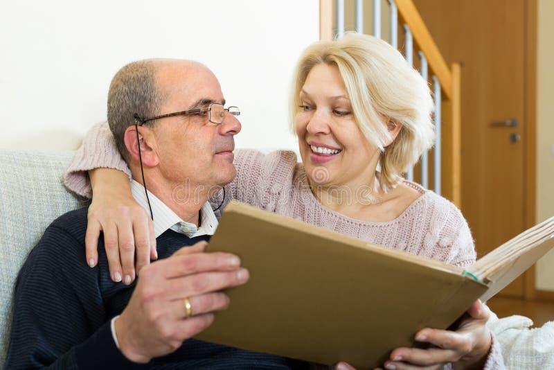 Старшие супруги с альбомом изображения крытым стоковая фотография