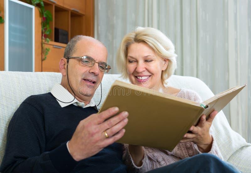 Старшие супруги с альбомом изображения крытым стоковые фото