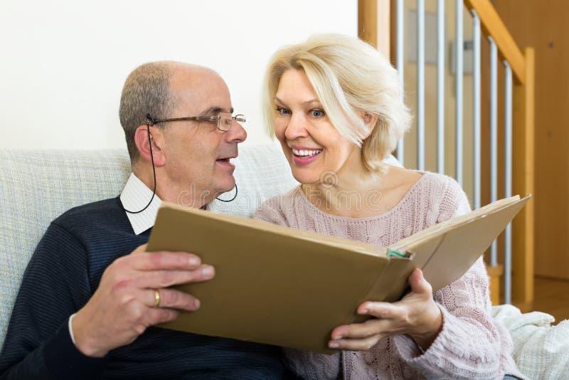 Старшие супруги с альбомом изображения крытым стоковое изображение rf