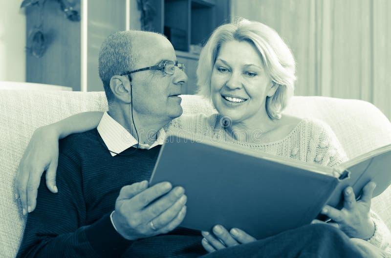 Старшие супруги с альбомом изображения крытым стоковые изображения