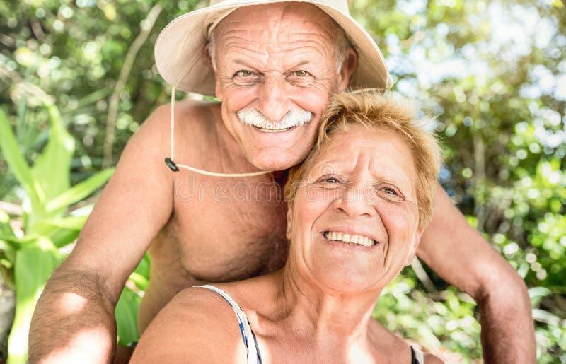 Старшие счастливые пары имея потеху принимая selfie на отключение Таиланда стоковое фото rf