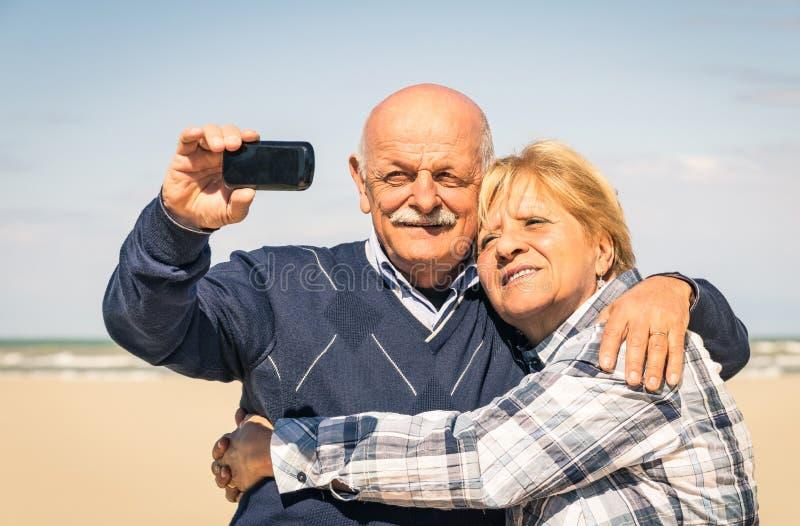 Старшие счастливые пары принимая selfie на пляж стоковое изображение
