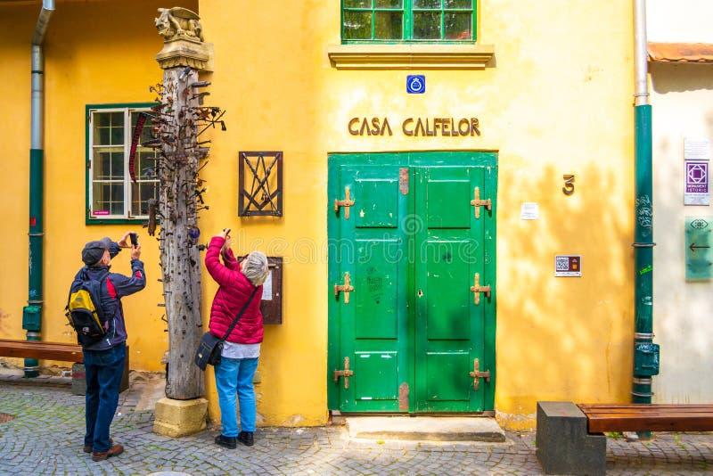 Старшие туристские пары фотографируя штендер подмастерьев, уникальный, старый деревянный поляк с ногтями в нем стоковое изображение rf