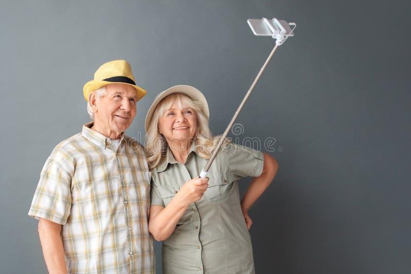 Старшие туристы в положении студии шляп пляжа изолированные на сером держа monopod принимая selfie на смотреть смартфона стоковая фотография