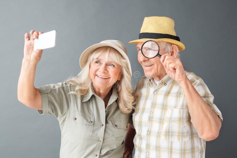 Старшие туристы в положении студии шляп пляжа изолированные на selfies серого увеличителя удерживания человека шаловливых принима стоковая фотография