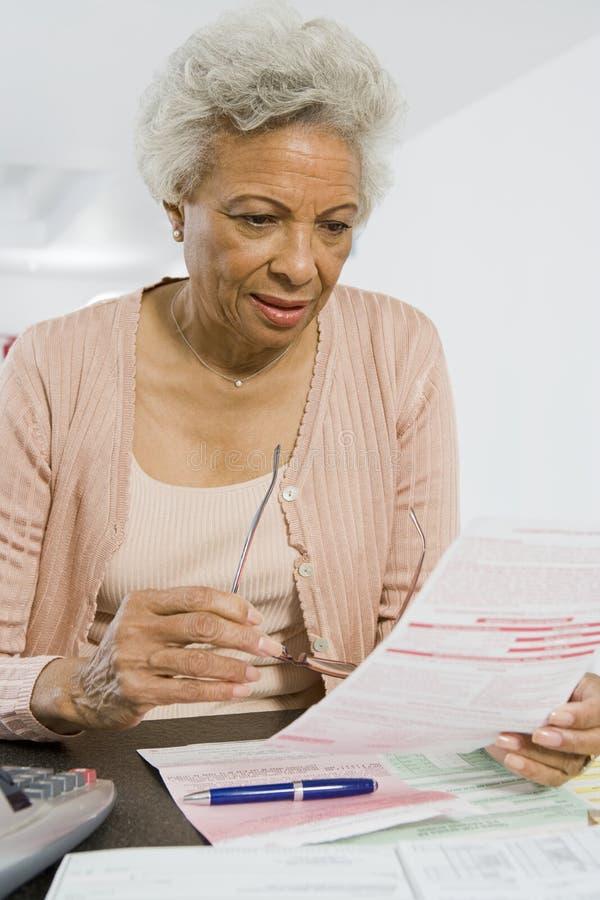 Старшие финансы дома чтения женщины стоковые фотографии rf