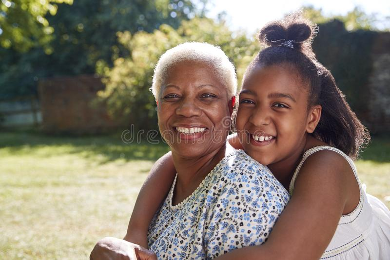 Старшие чернокожая женщина и внучка сидят обнимать снаружи стоковые фотографии rf