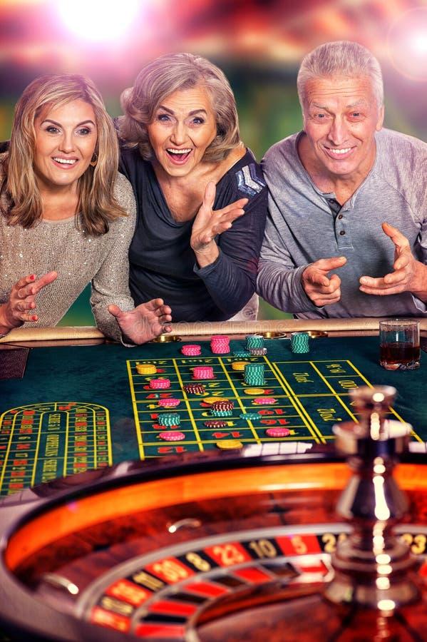Старшие люди играя в казино стоковое фото