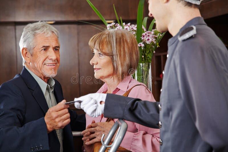 Старшие люди принимая ключевую карточку от консьержа стоковое фото