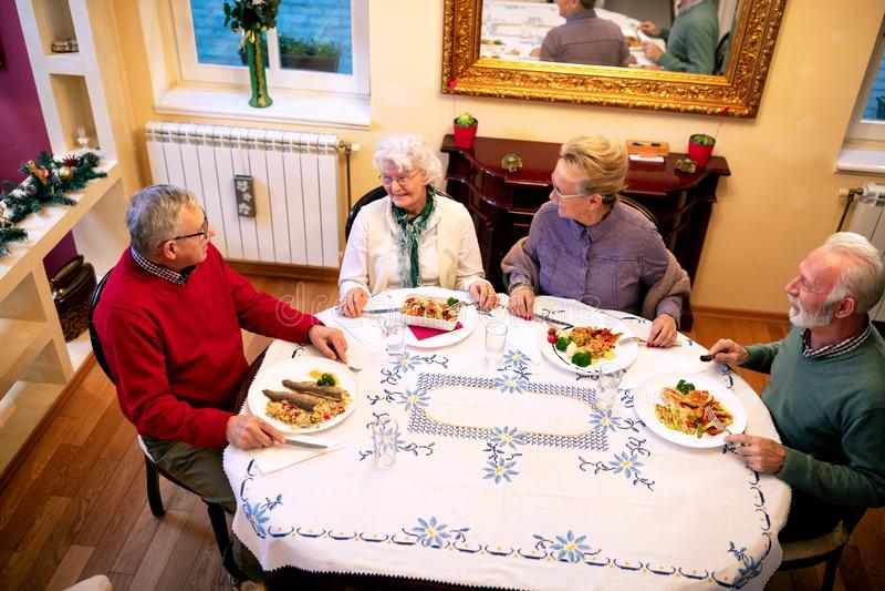 Старшии имея очень вкусный обедающий стоковое фото