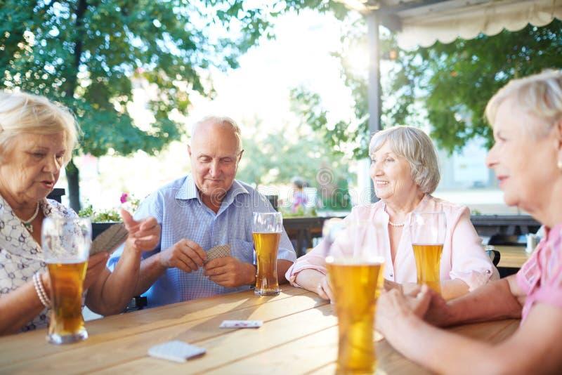 Старшии наслаждаясь карточной игрой стоковая фотография rf