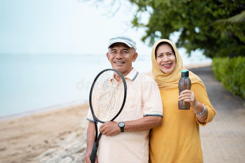 Старший азиатские человек и женщина усмехаясь с теннисом ракетки стоковые фото