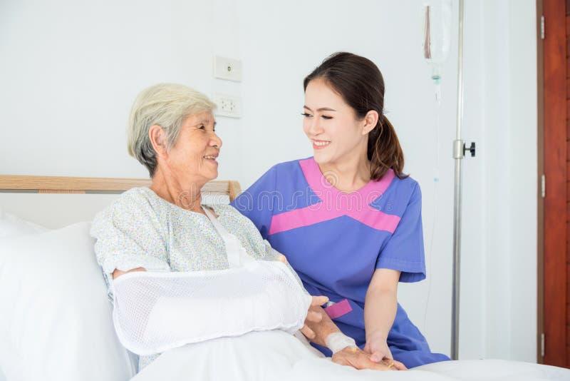 Старший азиатский женский пациент усмехаясь с медсестрой стоковые изображения