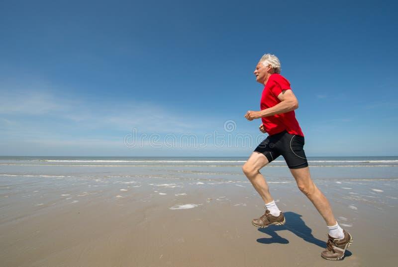 Старший бегун на пляже стоковое фото rf
