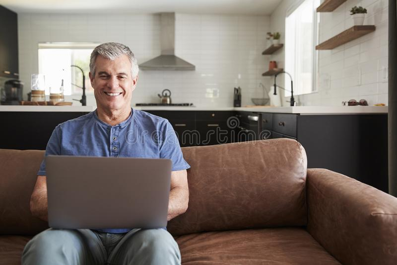Старший белый человек сидя на софе дома используя ноутбук стоковое изображение