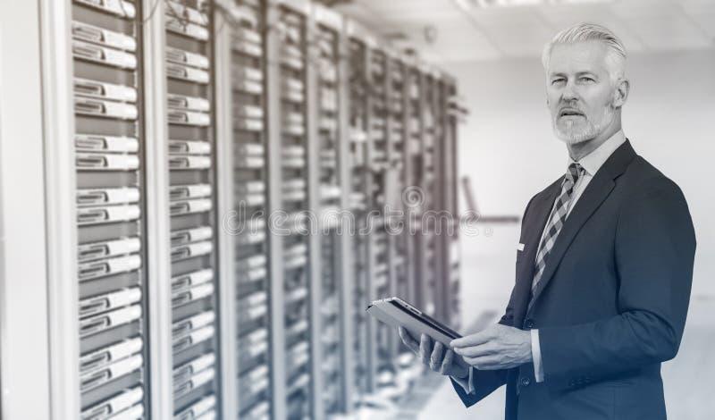 Старший бизнесмен в комнате сервера стоковое фото rf