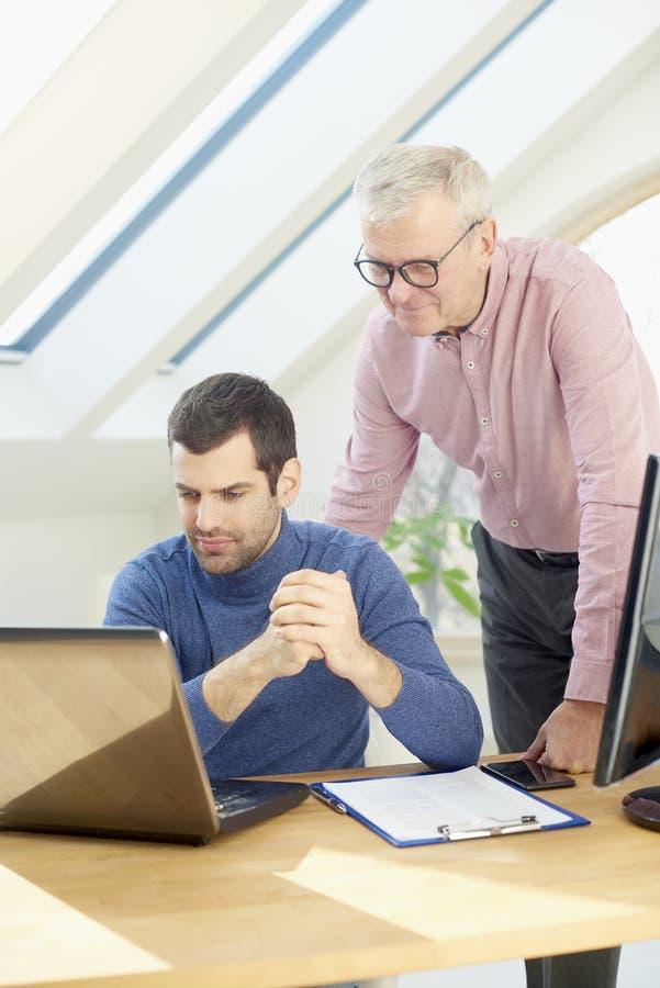 Старший бизнесмен давая adice к ее молодому коллеге стоковые изображения