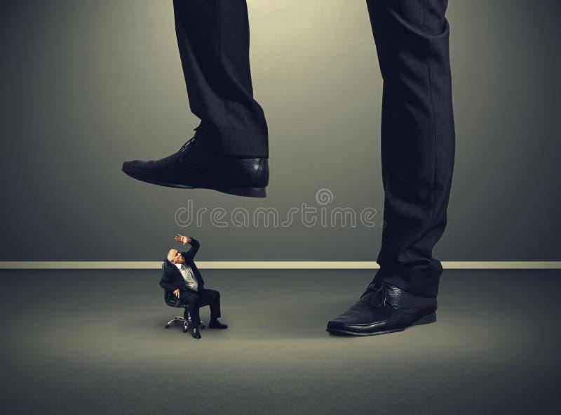 Старший бизнесмен под большой ногой его босс стоковое фото